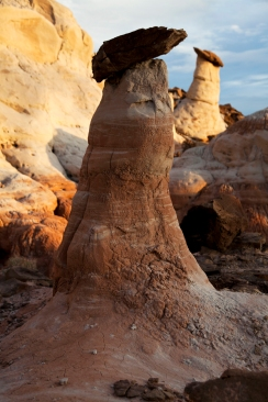 Formed by billions of freeze & thaw cycles and the umbrella-like protection of their capstones, Hoodoos slowly emerge from eroding landscapes. These two (on the Utah / Arizona border) seemingly doff their capstones to each other in recognition of their unique existence.